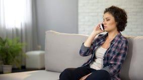 Belle femme parlant au téléphone, ayant la conversation sérieuse, recherchant le travail image libre de droits