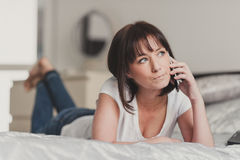 Belle femme parlant sur le smartphone dans sa chambre à coucher Image stock