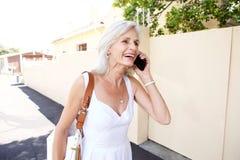 Belle femme plus âgée marchant et parlant au téléphone portable Image stock