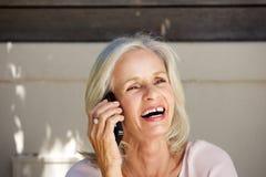 Belle femme plus âgée riant au téléphone portable dehors Photographie stock