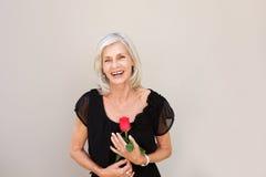 Belle femme plus âgée riant avec la rose de rouge dans le chemisier noir Photographie stock libre de droits