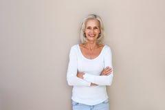 Belle femme plus âgée se tenant et souriant avec des bras croisés Photographie stock