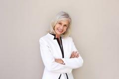Belle femme plus âgée souriant et se tenant avec des bras croisés Photos stock