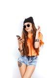 Belle femme portant dans le chapeau noir et la musique de écoute de T-shirt blanc près du mur blanc, jugeant un téléphone portabl Images stock