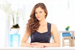 Belle femme posant à une table à l'intérieur Images stock