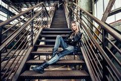 Belle femme posant l'équipement occasionnel de port avec la veste en cuir, les chaussures noires et les jeans à la mode Fille pos Photos libres de droits