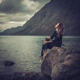Belle femme posant sur le rivage d'un lac sauvage, avec des montagnes sur le fond Image libre de droits