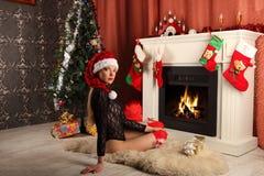 Belle femme près de la cheminée dans la maison d'hiver Noël selebrating Photo libre de droits