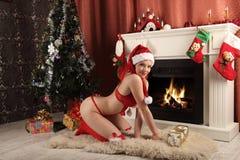 Belle femme près de la cheminée dans la maison d'hiver Noël selebrating Photographie stock