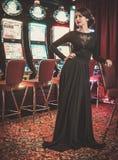 Belle femme près des machines à sous dans un intérieur de luxe de casino Photo stock