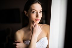 Belle femme près des rideaux de fenêtre et de regarder l'appareil-photo Photos stock