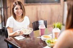 Belle femme prenant le déjeuner avec un ami Photo stock