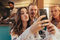 Belle femme prenant le selfie avec des amis Photos libres de droits