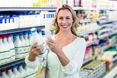 Belle femme prenant une photo de bouteille à lait Photographie stock