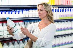 Belle femme prenant une photo de bouteille à lait Image libre de droits