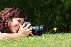 Belle femme prenant une photographie d'une fleur sur l'herbe Images stock