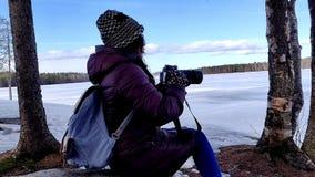Belle femme réfléchie prenant des photos en nature couverte par neige extérieure banque de vidéos