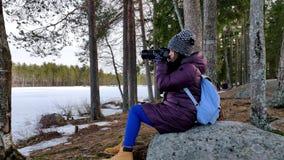 Belle femme réfléchie prenant des photos en nature couverte par neige banque de vidéos