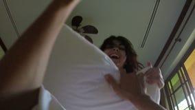 Belle femme réveillant l'homme s'asseyant sur lui se situant dans le lit dans des oreillers de combat de jeunes couples du matin  banque de vidéos