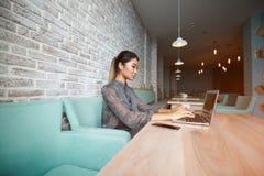 Belle femme rêvant de quelque chose tout en se reposant avec le filet-livre portatif dans la barre moderne de café, Photographie stock libre de droits