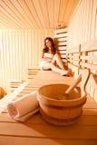 Belle femme Realxing dans le sauna finlandais Images stock