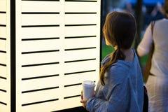 Belle femme regardant avec l'intérêt sur le panneau d'affichage vide décidant où aller Photos stock