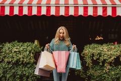 Belle femme regardant dans le sac à provisions avec l'excitation image stock