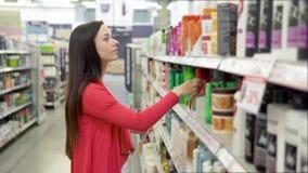 Belle femme regardant des cosm?tiques dans le supermarch? Fille attirante achetant les produits cosm?tiques Regard et choix banque de vidéos
