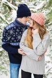 Belle femme regardant l'homme dans la forêt neigeuse parmi des sapins Photographie stock libre de droits