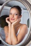 Belle femme regardant par la machine à laver photos libres de droits