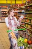 Belle femme regardant un certain produit dans un supermarché image stock