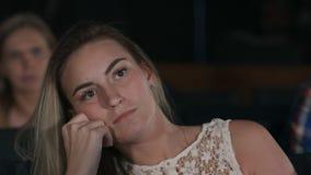 Belle femme regardant witting seul extrêmement ennuyé dans un hall vide de cinéma observant un film ennuyeux Photo stock