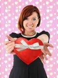 Belle femme rouge de cheveux tenant la boîte d'anniversaire de boîte de forme de coeur Photos stock