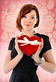 Belle femme rouge de cheveux tenant la boîte d'anniversaire de boîte de forme de coeur Images stock