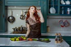 Belle femme rousse dans la cuisine Image libre de droits
