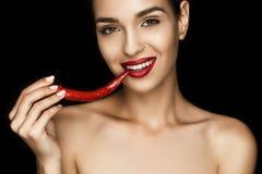 Belle femme séduisante nue avec les lèvres rouges tenant le poivre de piment photos libres de droits