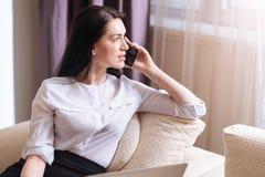 Belle femme sérieuse mettant un téléphone à son oreille Photos libres de droits