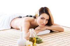 Belle femme s'étendant sur un tapis ayant une odeur de l'arome dans le salon de station thermale Image stock