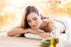 Belle femme s'étendant sur un tapis ayant une odeur de l'arome dans le salon de station thermale Photos stock