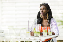 Belle femme s'asseyant à une table et à des amis de attente Image stock