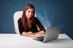 Belle femme s'asseyant au bureau et tapant sur l'ordinateur portable avec l'abstra Images libres de droits