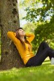 Belle femme s'asseyant contre l'arbre en parc Photos stock