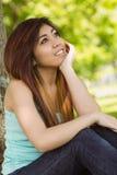 Belle femme s'asseyant contre l'arbre en parc Photographie stock