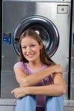 Belle femme s'asseyant contre la machine à laver image stock
