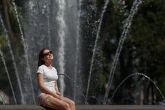 Belle femme s'asseyant dans des lunettes de soleil sur le fond de fontaine Image stock