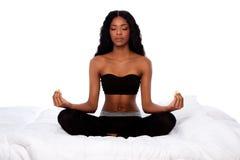 Belle femme s'asseyant dans la pose de yoga de lotus sur le lit Photo libre de droits