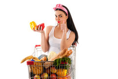 Belle femme s'asseyant dans le chariot à supermarché Photos stock