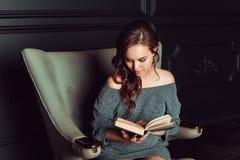 Belle femme s'asseyant dans une chaise et lisant un livre photo libre de droits