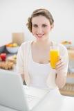 Belle femme s'asseyant devant son ordinateur portable dans sa cuisine tout en tenant un verre de jus d'orange Image stock