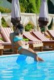 Belle femme s'asseyant par la piscine image stock